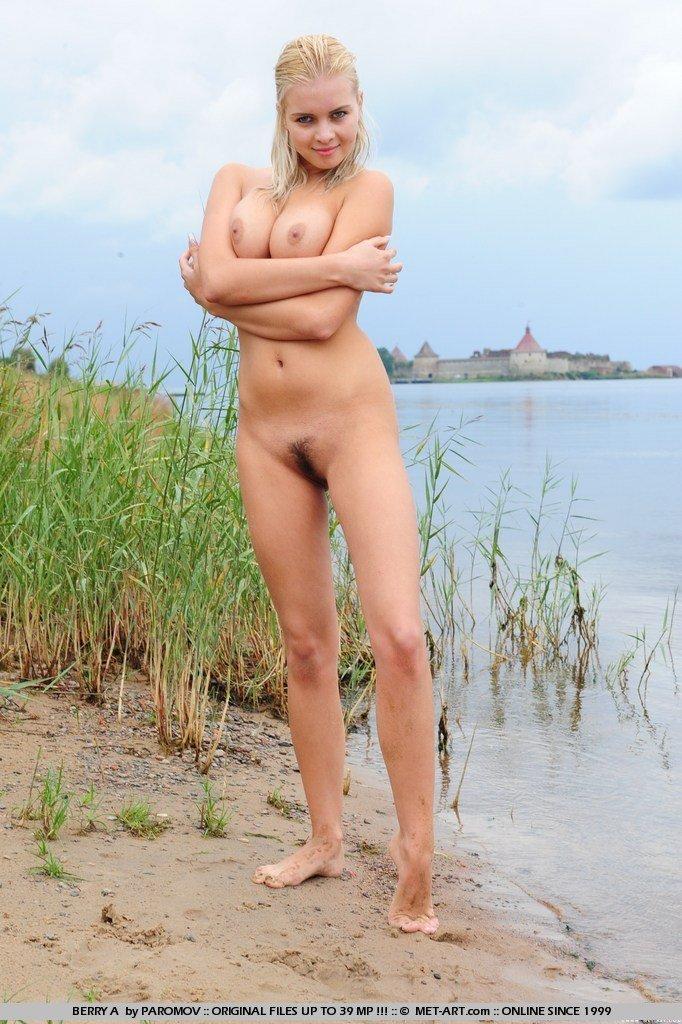 Классная блондиночка Berry A спускает майку около воды и демонстрирует грудь и лохматую вульву. Порно блондиночка.