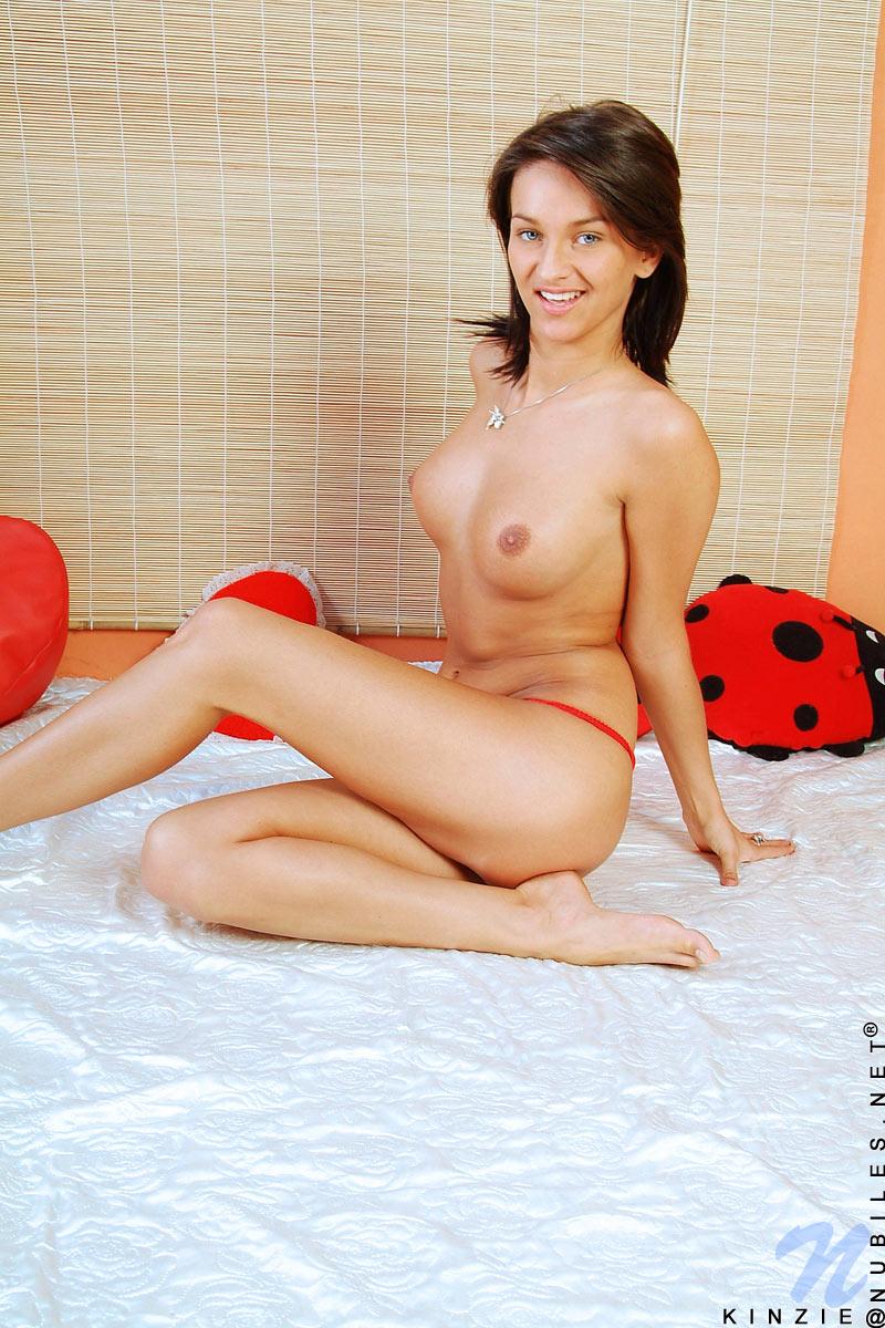 Сочная брюнетка-подросток Kinzie Nubiles снимает красное белье на двуспальной постели. Порно брюнетка.
