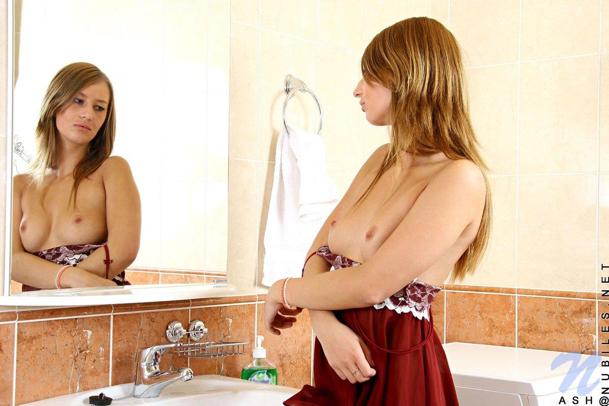 Сексуальная малышка Ash Nubiles снимает лифчик в ванной и ублажает свою пизду струями водоема. Порно малышка.